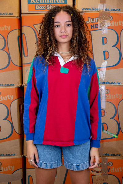 Vertically striped in red and blue, this rugby style sweater has green shoulder pads, underarms and a green chest patch on the front. With a white collar and matching white buttons