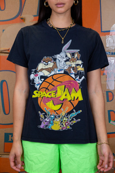 the model wears a black tee with a space jam graphic on the front