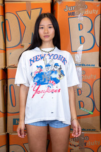 the model wears a distressed white tee with a looney tunes and new york yankees graphic on the front
