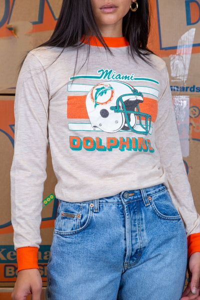 the model wears a white long sleeve wth a miami dolphins graphic on the front