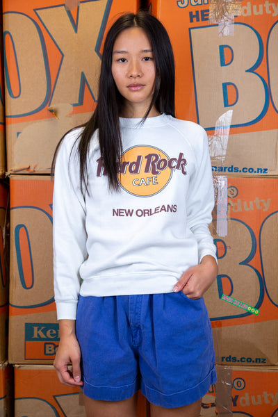 the model wears a white sweater with a hard rock new orleans spell out on the front