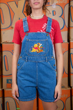 Load image into Gallery viewer, Mid wash blue in colour, these dungarees have a colour appliqué of Pooh Bear and Tigger amongst flowers on the front pocket. Finished off with brown stitching, belt loops, flowers embroidered on the back pockets and Pooh branding on the buttons