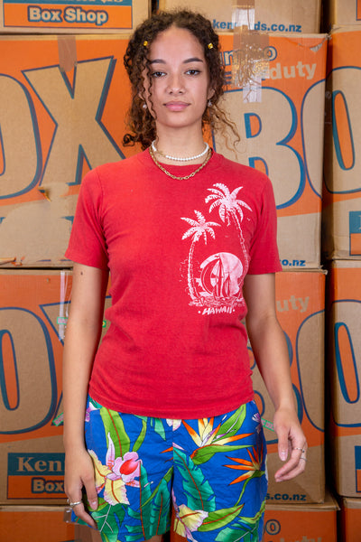 The model is wearing a small red tee featuring the Hawaii logo on the left side
