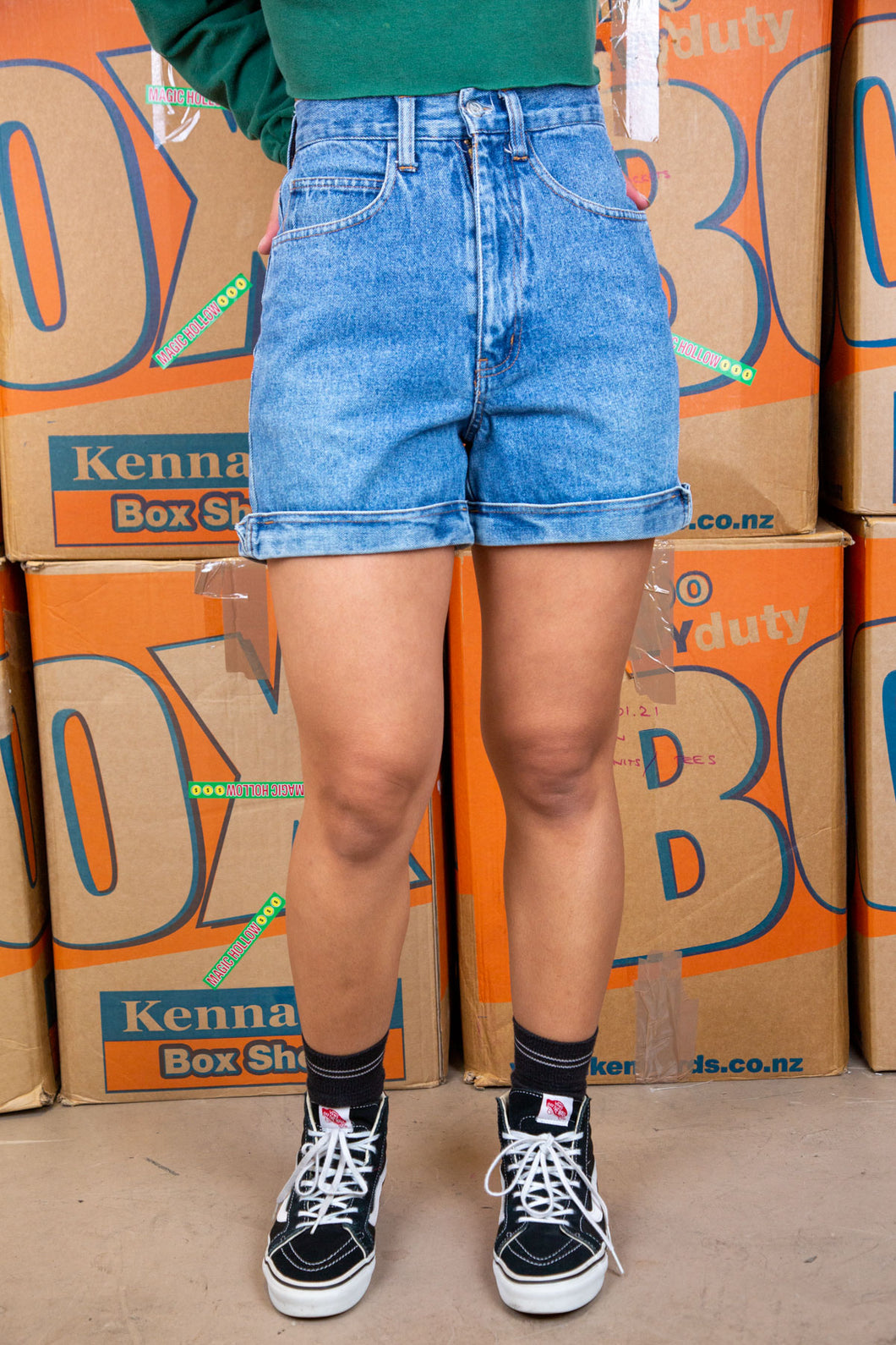 Mid-wash blue, these denim shorts have brown stitching, foldable rims and No Excuses branding on the button, back/right pocket and the back waistline.