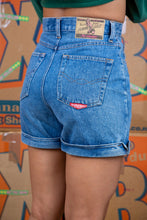 Load image into Gallery viewer,  Mid-wash blue, these denim shorts have brown stitching, foldable rims and No Excuses branding on the button, back/right pocket and the back waistline.
