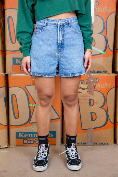 Light wash blue, these denim shorts have brown stitching, pentagon-shaped back pockets, belt loop and Bongo branding on the button, front/right pocket and back waistline.