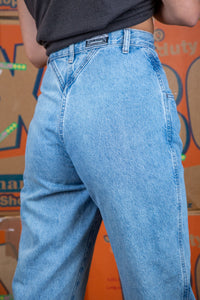 Light-wash blue, these jeans have a tailored waist, mom-jean style, white stitching and branding on the back waistline, left pocket, domes and button.