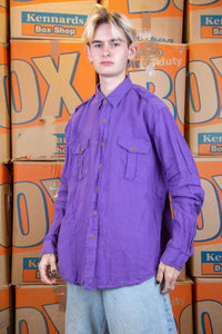 Purple in colour, this button-up has a linen feel with brown buttons and double breast pockets.