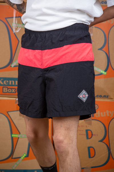 These must-have shorts are black with a luminous pink horizontal stripe across the middle. With a diamond-shaped Ocean Pacific plaque on the left leg, these shorts are not only cool as f*ck, but they can double up as togs!