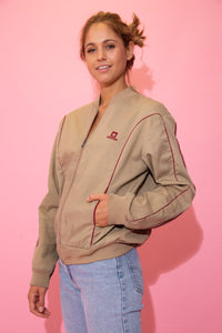 Brown in colour, this jacket has maroon trim across the bodice with a maroon Converse logo on the left chest. With a ribbed neckline, cuffs and waistline, in a bomber jacket style