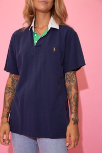 Navy blue Ralph Lauren polo in a ribbed material with a white collar, green neckline, white buttons and a colour Ralph Lauren logo on the left chest.