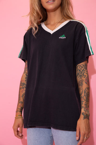 Black tee in a v-neck cut with a white neckline, the signature three white lines down the shoulders and green colouring in between. Finished off with Adidas branding on the left chest in white and green.