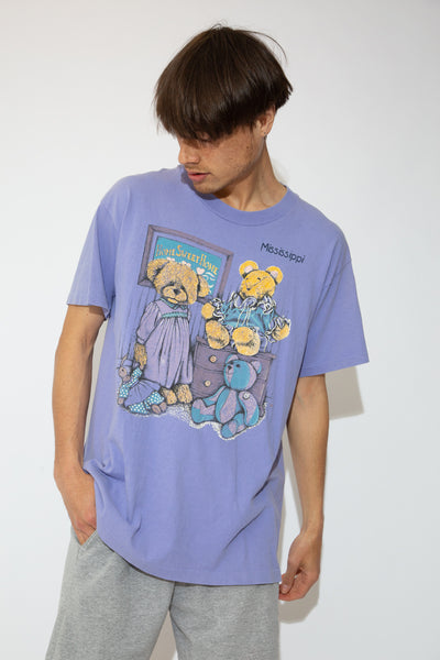 Lilac purple tee with an old school print of a bear in a bedroom on the front and Mississippi on the left/front. Stretched out neckline adds to the baggy fit.