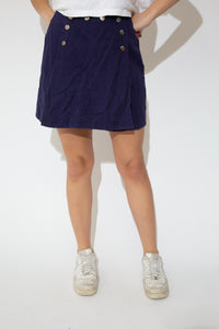 This skort is purple in colour with a denim-like texture. Shorts with a flap over the front and branding on the metal buttons that border the flap.