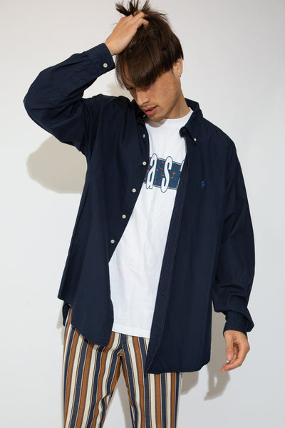 This sick Ralph Lauren button-up is navy blue in colour with shell-like buttons and a blue Ralph Lauren logo on the left front.