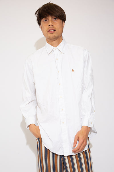 This slick button-up is white in colour with the Ralph Lauren logo on the left chest. Finished off with shell-like buttons down the front and on the sleeves.