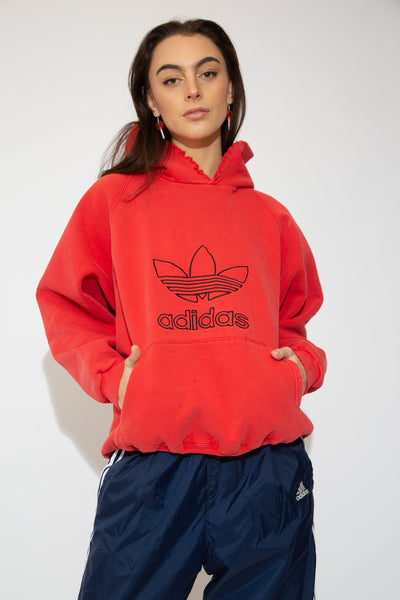 Red in colour with 'Adidas' and the logo embroidered in black on the front, this oversized jumper is a vintage must-have. Finished off with a hood and a kangaroo-pouch style pocket for that cosy, comfy fit.