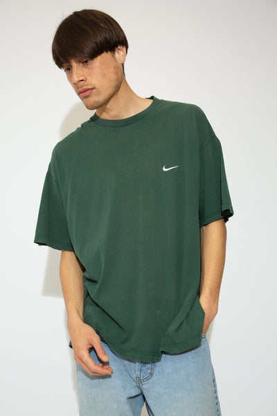 Forest green with the white Nike logo embroidered on the left chest, this oversized tee has a stretched out, ribbed neckline that adds to the boxy fit.
