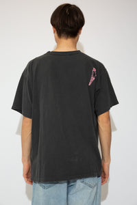 Faded black, single-stitch tee with 'Daytona Beach Paradise Resort' printed on the front. Stretched out neckline adds to the baggy fit. Pink bird print on back right shoulder.
