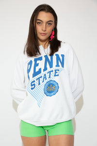 This white sweater has a blue and white print of 'Penn State' on the front with the logo below. A v-cutout on the neckline and baggy fit adds to the vintage style.