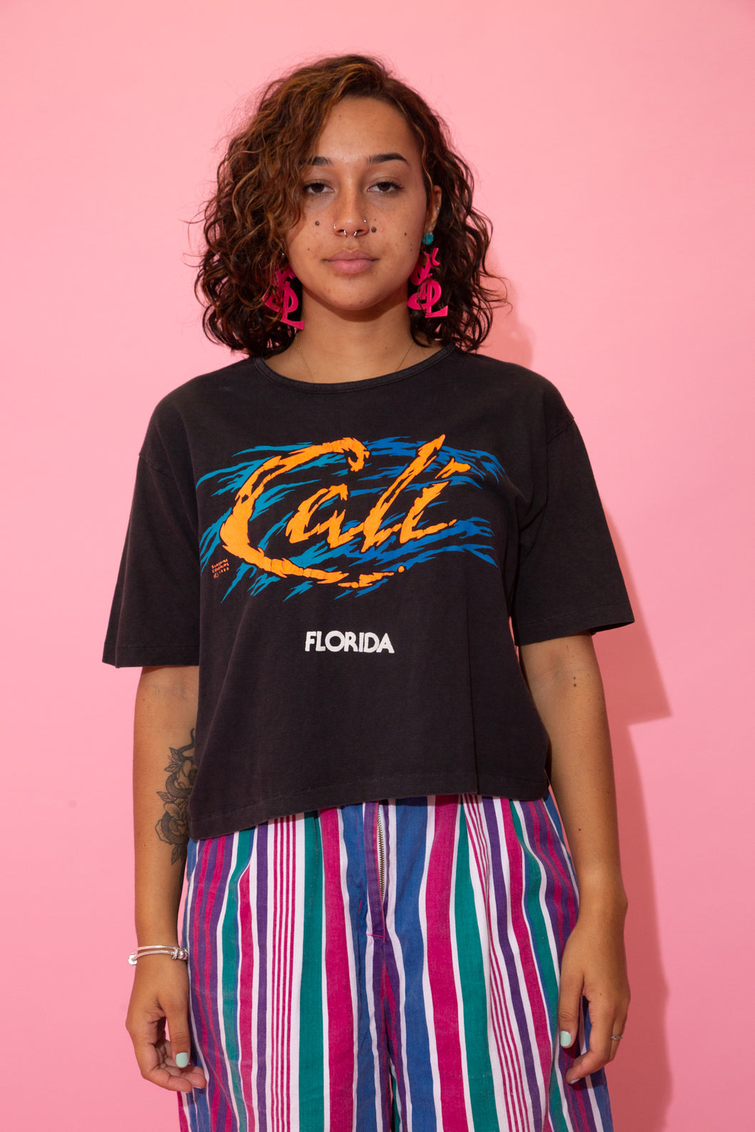 the model wears a black crop with a cali florida graphic on the front
