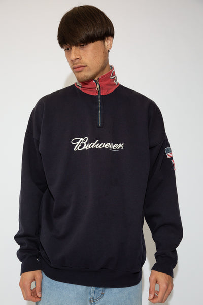 model is wearing a quarter zip sweater featuring the iconic Budweiser