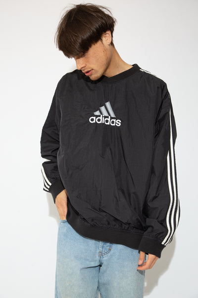 This black sweater has a windbreaker outer shell and a soft inner lining. With the three Adidas lines down the sleeves, zip on the left side and the Adidas logo on the front, this is a vintage must-have.