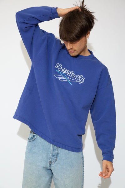 This sweater is indigo in colour with a white and blue appliqué of 'Reebok' and the logo on the front. Ribbed neckline and cuffs accentuate boxy fit.