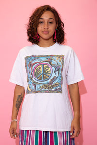 the model wears a white tee with a peace sign graphic on the front
