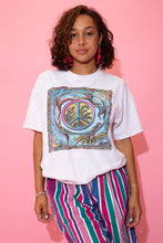 Load image into Gallery viewer, the model wears a white tee with a peace sign graphic on the front