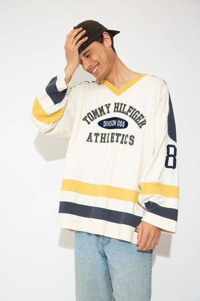 This long sleeve tee is off-white with a yellow v-neckline, blue Tommy branding on the front and right arm and blue and yellow horizontal stripes across the bottom. Repping 88 on the back and left left sleeve in an old-school football jersey style.