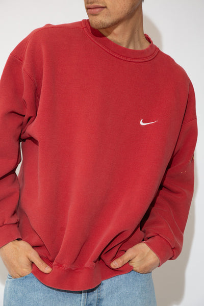 model is wearing a red Nike sweater that feartures a white tick on the left side