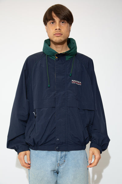 This Nautica jacket  is a thick rain jacket material with a navy blue bodice and dark green collar. Finished off with branding on the left chest, drawstrings, a zip and matching navy blue domes.