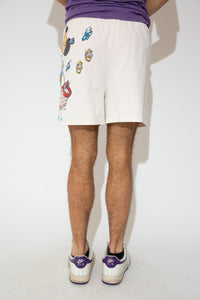 White, high-waisted shorts with a large print of Mickey Mouse catching butterflies on the left side and an elasticated waist. Dated 1973.