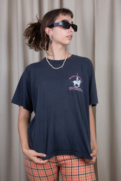 the model wears a faded black tee with a polo graphic on the chest and back