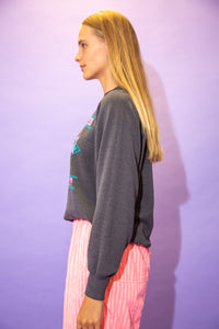 the model wears a grey sweater with a rock n roll spell out graphic on the front