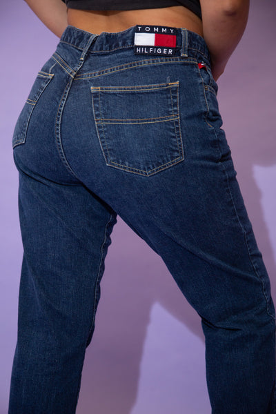Dark-wash blue in colour, these jeans are in a straight leg fit with brown stitching and Tommy Hilfiger branding on the button, front right pocket and back waistline.