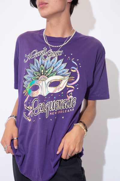 Purple single stitch tee with sparkly colourful print of a mask and 'Mardi Gras Masquerade New Orleans' printed across the tee. Dated 1991