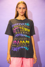 Load image into Gallery viewer, the model wears a faded black tee with an allover rainbow graphic