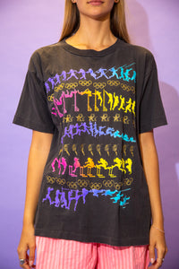 the model wears a faded black tee with an allover rainbow graphic