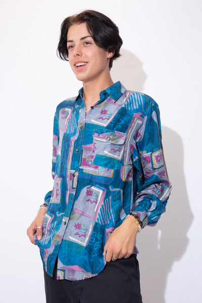Silky smooth and sexy as f*ck, this baddie button-up is covered in an allover blue and purple abstract print with a left chest pocket and black buttons.