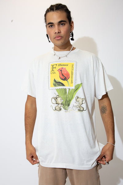 White single stitch tee with a print of two mice watering a tulip on the front in a lil post stamp frame.