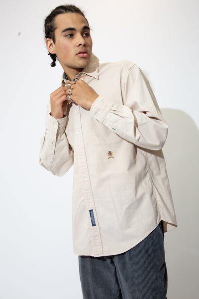 Light brown button-up with white buttons and the Tommy Hilfiger lion emblem below the left chest pocket.