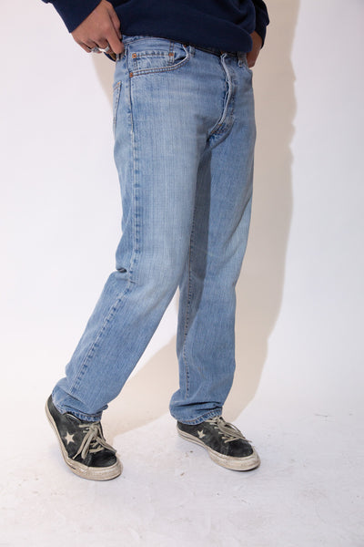 Light wash jeans in a straight leg fit with light brown stitching and Levi's branding on the buttons, domes, back waistline and back pocket.