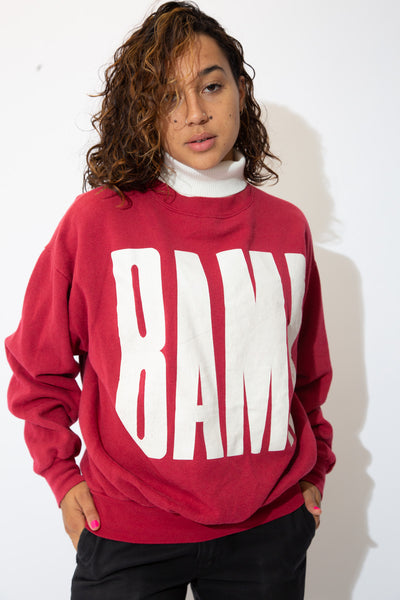 the model wears a fucshia sweater with a bama spell out