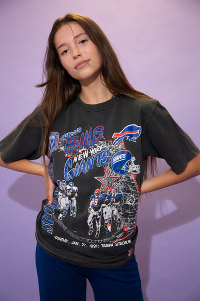 Black in colour, this single stitch tee has a large navy blue and red print repping the Buffalo Bills and the New York Giants on the front. Dated 1989 with the Super Bowl logo and a West Coast football print
