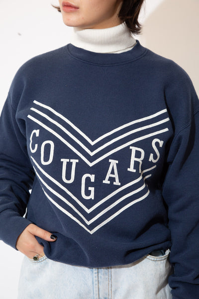 the model wears a navy cougars sweater