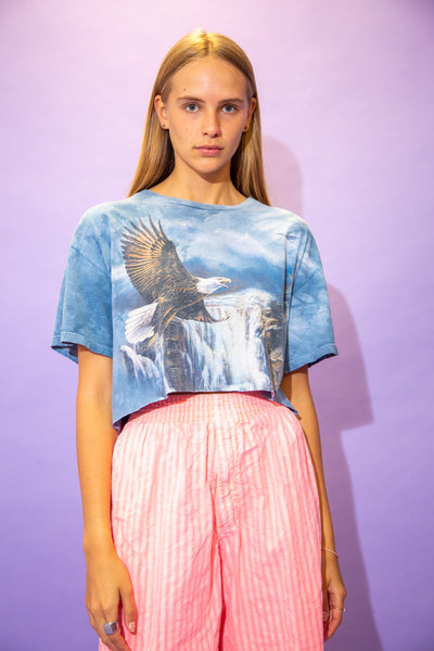 the model wears a blue tie dyed cropped tee with an eagle graphic on the front