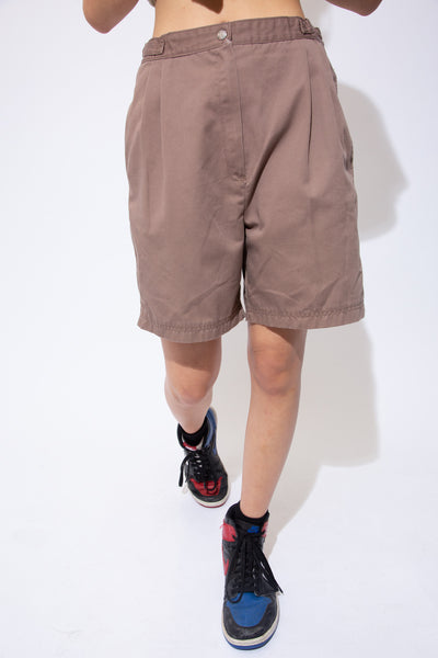 Chocolate brown tailored shorts with tightening straps around the waistline, pockets and a zip and dome closure.