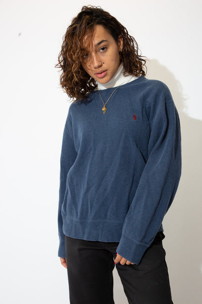 the model wears a navy blue sweater
